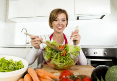 Junge schöne Hauptkochfrau an der modernen Küche, die das Gemüsesalatschüssellächeln glücklich vorbereitet Lizenzfreie Stockbilder