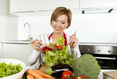 Junge schöne Hauptkochfrau an der modernen Küche, die das Gemüsesalatschüssellächeln glücklich vorbereitet Stockfotografie