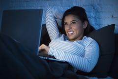 Junge schöne hispanische Frau auf dem Arbeiten des Betts zu Hause glücklich auf Laptop-Computer nachts Stockfoto