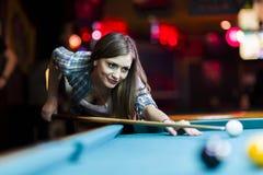 Junge schöne junge Dame, die darauf abzielt, den Snookerschuß zu nehmen Lizenzfreies Stockbild