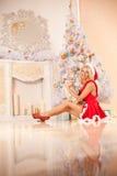 Junge schöne lächelnde Sankt-Frau nahe dem Weihnachtsbaum mit Stockfoto