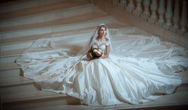 Junge schöne luxuriöse Frau im Hochzeitskleid, das auf Treppe sitzt, tritt in Halbdunkel Braut mit enormem Hochzeitskleid Lizenzfreies Stockfoto