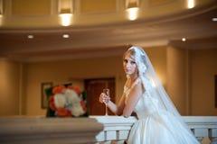 Junge schöne luxuriöse Frau im Hochzeitskleid, das im luxuriösen Innenraum aufwirft Braut mit enormem Hochzeitskleid im majestäti Stockbild