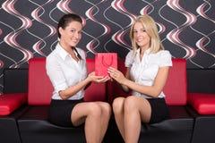 Junge schöne Mädchen, die auf dem Sofa mit Geschenk sitzen Lizenzfreies Stockfoto