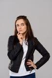 Junge schöne Mädchenaufstellung, denkend über purpurrotem Hintergrund Stockbild