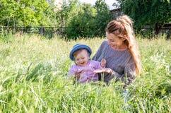 Junge schöne Mutter, die im Gras mit ihrer kleinen Babytochter in Panama spielt Lizenzfreie Stockfotos