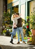 Junge schöne Paare in der Liebe, die auf der Straße feiert Valentinsgrußtag mit rosafarbenem Geschenk küsst Stockbild
