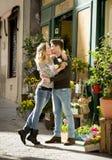 Junge schöne Paare in der Liebe, die auf der Straße feiert Valentinsgrußtag mit rosafarbenem Geschenk küsst Lizenzfreies Stockbild