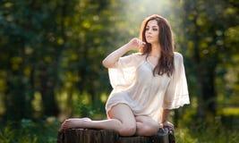 Junge schöne rote Haarfrau, die eine transparente weiße Bluse aufwirft auf einem Stumpf in einem grüner Waldmodernen sexy Mädchen Stockbild