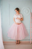Junge schöne schwangere Frau, die nahe Fenster aufwirft Stockfotografie