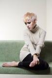 Junge schöne traurige Frau, die auf Sofa sitzt Stockfoto