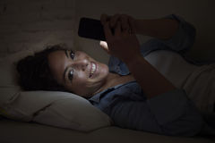 Junge Schönheit, die auf Hauptcouch unter Verwendung des simsenden Lächelns des Handys glücklich liegt Lizenzfreies Stockbild