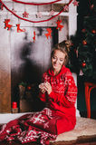 Junge Schönheit, die in den roten warmen Pyjamas mit den skandinavischen Verzierungen sitzen nahe dekorativem Kamin und trinkende Stockbild