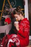Junge Schönheit, die in den roten warmen Pyjamas mit den skandinavischen Verzierungen sitzen nahe dekorativem Kamin und trinkende Stockfoto