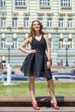 Junge Schönheit im schwarzen Kleid, das draußen in sonnigem uns aufwirft Lizenzfreie Stockfotos