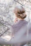 Junge Schönheit nahe Bäumen in der Blüte im Frühjahr Frisurengrenze Stockfoto