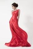 Junge Schönheitsfrau in flatterndem rotem Kleid. Weißer Hintergrund. Stockbild