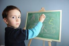 Junge schreibt auf einen Armaturenbrett Stockbilder