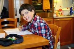 Junge schreibt auf sein Notizbuch Stockfotos