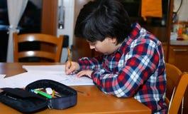 Junge schreibt auf sein Notizbuch Stockfoto