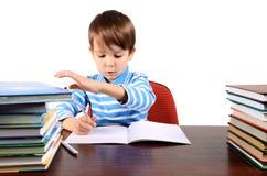 Junge schreibt und nimmt ein Buch gleichzeitig Stockbild