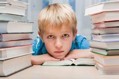 Junge am Schreibtisch mit Büchern Stockbilder
