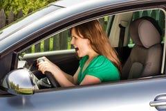 Junge schreiende Frau beim Fahren des Autos Stockbilder