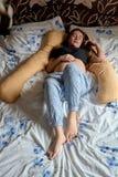 Junge-schwangere Frau Schwangere Sch?nheit schl?ft auf Mutterschaftskissen im Bett lizenzfreie stockfotografie