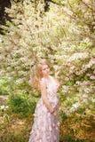 Junge schwangeres womani n rosa mit Blumenkleid, das die blühenden Bäume steht Stockfotografie