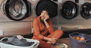 Junge Schwarzafrikaner Amerikanerin, die ihre in einer automatischen Wäscherei gewaschen zu werden Kleidung, wartet stock footage