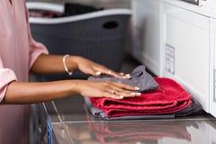 Junge Schwarzafrikaner Amerikanerin, die ihre Kleidung in einer automatischen Wäscherei wäscht lizenzfreies stockfoto