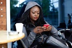 Junge schwarze Frau beschäftigt mit Handy Lizenzfreie Stockbilder