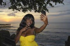 Junge schwarze Frau des attraktiven und bezaubernden Afroamerikaners im schicken Sommerkleid, das selfie Bild oder Video am Handy Stockbilder