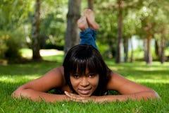 Junge schwarze Frau, die auf dem Gras liegt Stockbilder
