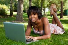 Junge schwarze Frau, die einen Laptop verwendet lizenzfreies stockbild