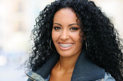 Junge schwarze Frau, die mit Klammern lächelt Stockbild