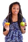 Junge schwarze Frau, die Orangensaft trinkt Lizenzfreie Stockfotos
