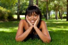 Junge schwarze Frau, die sich auf dem Gras hinlegt lizenzfreie stockfotos