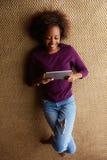 Junge schwarze Frau, die sich mit digitaler Tablette hinlegt Stockfotos