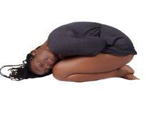 Junge schwarze Frau im grauen Knitkleid auf Knien Stockfoto