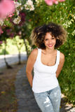 Junge schwarze Frau mit Afrofrisur lächelnd im städtischen Park Lizenzfreies Stockbild