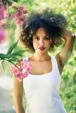 Junge schwarze Frau mit Afrofrisur lächelnd im städtischen Park stockbild