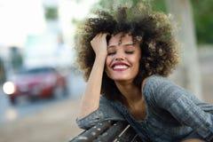 Junge schwarze Frau mit Afrofrisur lächelnd im städtischen backgroun Stockfoto