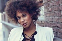 Junge schwarze Frau mit der Afrofrisur, die im städtischen backgrou steht stockfotografie