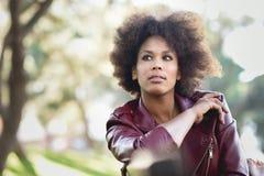 Junge schwarze Frau mit der Afrofrisur, die im städtischen backgrou steht lizenzfreie stockfotografie