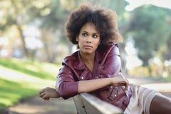 Junge schwarze Frau mit der Afrofrisur, die im städtischen backgrou steht lizenzfreie stockbilder