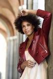 Junge schwarze Frau mit der Afrofrisur, die im städtischen backgrou steht Lizenzfreie Stockfotos