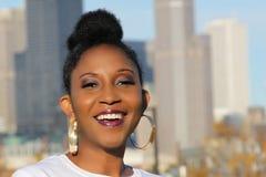 Junge schwarze Frau mit großen Bandohrringen, schmackhaftem Make-up und großem Lächeln Stockbilder