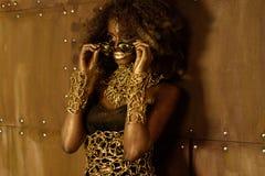 Junge schwarze Frau mit tragendem Zubehör des Afrohaares Goldund Make-up, das auf die Sonnenbrille, weg schauend sich setzt Stockfotos