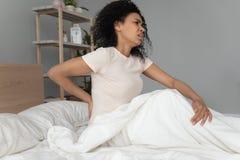 Junge schwarze Frau sitzen auf dem Bett, das hinteres Fühlung backpain berührt stockfoto